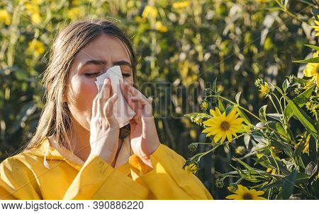 Cold Flu Season, Runny Nose. Flowering Trees In Background. Young Girl Sneezing And Holding Paper Ti
