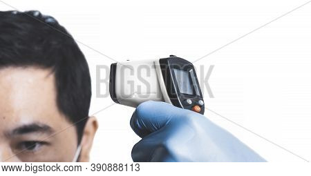 The Doctor Is Measuring The Asian Man Patient's Temperature With An Infrared Thermometer On White Co