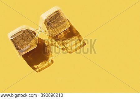 Close Up Hourglass Clock With Golden Sand On Yellow Background With Hard Shadow. Concept For Busines