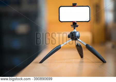 A Mobile Phone Mounted On A Tripod For Teaching Students Online.