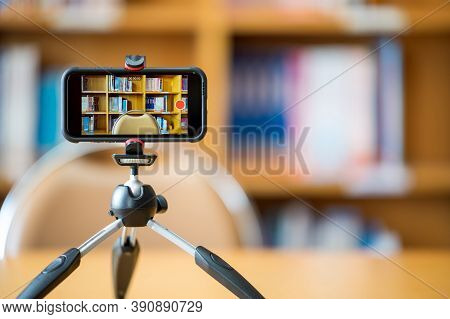 A Mobile Phone Mounted On A Tripod Is Used To Teach Students Online At The Library.