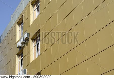 Yellow Metal Exterior Siding Of A Building. Wall Of A Corporate Building With Windows And Air Condit