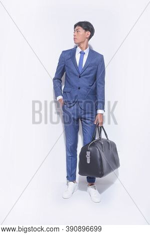 full length young handsome businessman  wearing blue suit with white shirt ,tie and blue pants with white sneaker holding big black handbag