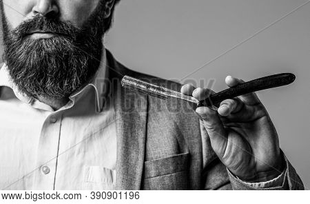 Vintage Straight Razor. Man In Barbershop. Handsome Bearded Hairdresser Is Holding A Straight Razor