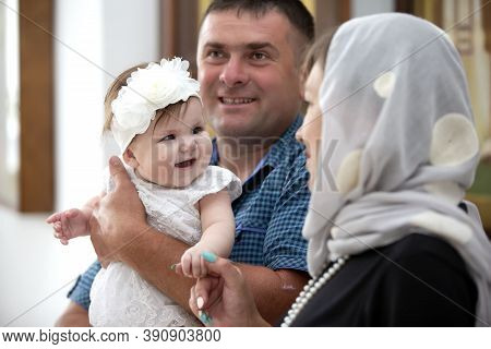 July 15, 2020 Belarus, Gomil. Central Church. Orthodox Baptism Of A Child. The Godparents Are Holdin
