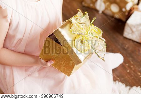 Сhild's  Hands Holding Gold Gift Box. Christmas, Hew Year, Birthday Concept. Festive Background With
