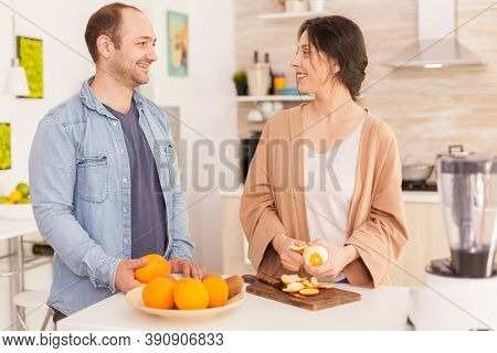Couple Smiling At Each Other While Preparing Nutritious Smoothie. Woman Peeling Off Orange. Healthy