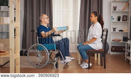 Senior Man In Wheelchair Training For Muscle Injury With Therapist. Disabled Handicapped Old Person