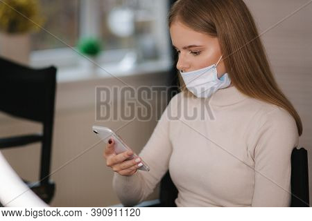 Female Customer In Beauty Salon Sitting On Hight Chair In Medical Mask And Use Phone. Beautiful Youn