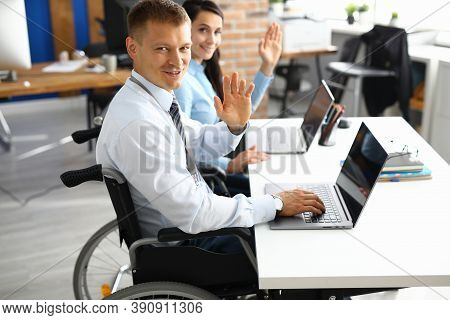 Businessman In Wheelchair And Businesswoman At Table Are Smiling And Raised Their Hands In Greeting.