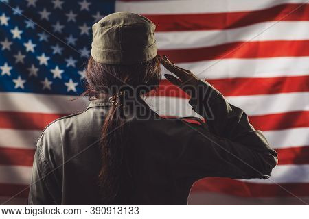 Veterans Day, Memorial Day, Independence Day. A Female Soldier Saluting Against The Background Of Th