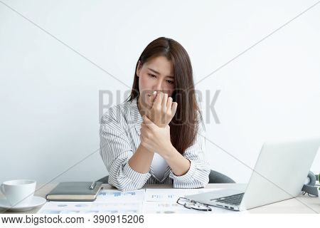 An Asian Woman Is Sitting Overtime With Her Laptop And Her Wrist Aches While Working At The Office.