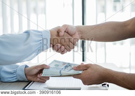 Photo Of Businessmen Shaking Hands And Dollar Note, Sign A Contract To Bribe Corruption In The Compa