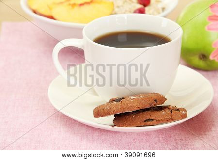 cup of coffee with cookies and fruits on table
