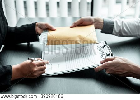 Businessman Giving Bribe Money In The Envelope To Businesswoman To Bribing Deal Contract In A Corrup