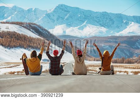 Four Happy Friends Sits With Raised Arms On Straight Mountains Road And Having Fun. Travel Concept