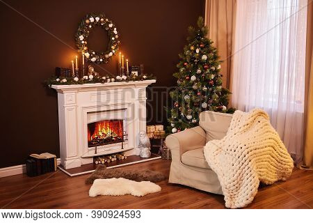 House In Christmas. Dark Living Room Interior With Comfortable Armchair Next To The Fireplace Decora