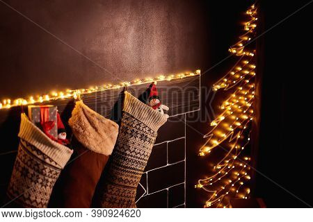 Beautifully Decorated Christmas Socks Hanging On A Painted Fireplace Waiting For Presents. Toy Snowm