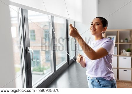 people and leisure concept - happy young african american woman opening window roller blinds at home