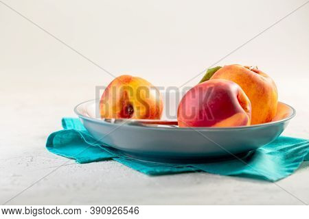 Ripe Organic Nectarines In A White Plate On A Linen Napkin. Healthy Eating Concept. Fruit Antioxidan
