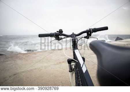Close-up Of Bicycle Handlebar On The Beach On Rainy Day With Waves