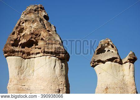 Fairy Chimneys On Blue Sky Background. Tuff Stone Formations. Geological Wonders Of Cappadocia.