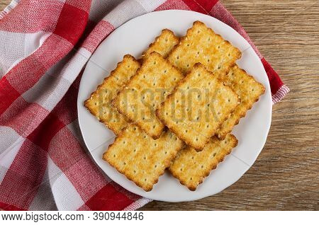 Crunchy Cookies With Sesame In White Plate On Checkered Napkin On Wooden Table. Top View