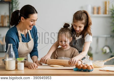 Happy loving family are preparing bakery together. Mother and children daughters girls are cooking cookies and having fun in the kitchen. Homemade food and little helper.