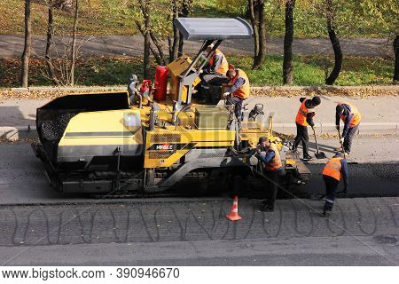 Russia, Vladivostok, October 21, 2020 : Paver And Road Workers In Orange Vests. Road Works To Replac