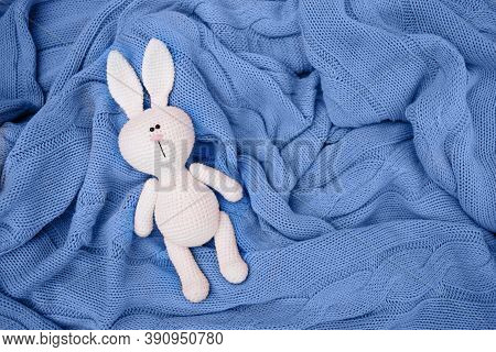 A Small Knitted Amigurumi Baby Rabbit Is On A Blue Blanket, Flat Lay, Top View