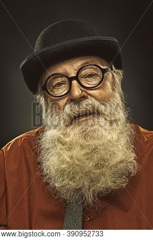 Portrait of an old-fashioned old man with a white beard in a bowler hat and round glasses. Old age. Black background.