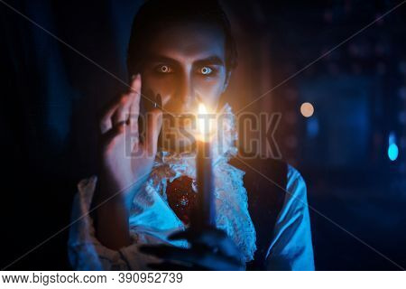 A bloodthirsty vampire aristocrat walks through the castle with a candle in his hands. 19th century style. Halloween.
