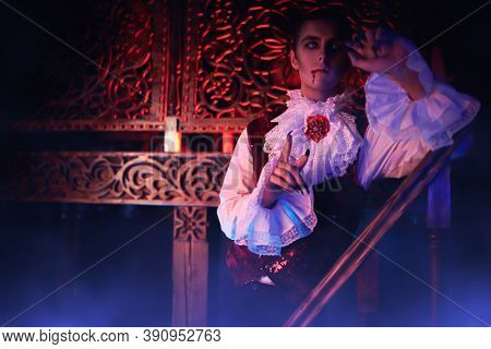 A bloodthirsty vampire aristocrat is posing on stair of castle in the night. 19th century style. Halloween.