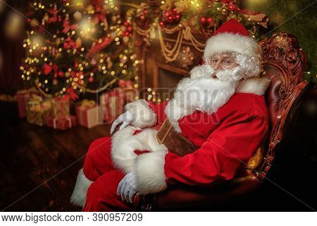 Santa Claus sits in an armchair in a beautiful Christmas interior. Christmas and New Year concept.