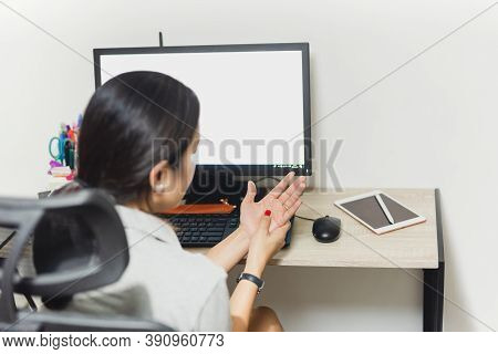 Woman Pressing The Middle Of Her Palm With Her Thumb To Relieve Pain By Use Of Computer.