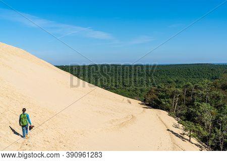 Single Woman Walking Down From The Dune Du Pilat In Western France