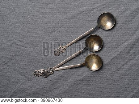 Ancient Metal Tablespoons On Grey Fabric Close-up
