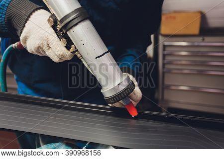 Glazier Applying Rubber Sealing To Windshield In Garage.