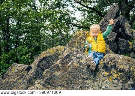 Little Boy Hiking In Mountins, Small Adventure. Child In Rocky Green Forest Having Fun.