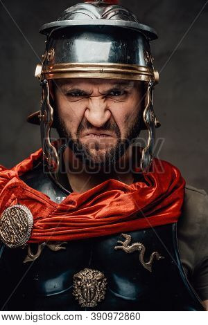 Mad And Savage Armoured Roman Soldier Dressed In Black Armour And Red Mantle With Helmet Posing With