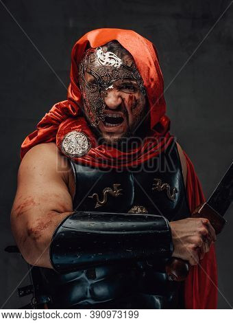 Savage Roman Slayer With Blood On His Face Dressed In Red Cloak And Weared With Mask Screams Holding