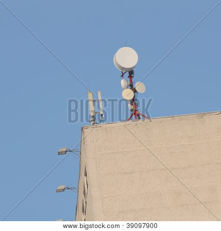 Cell Phone Towers On Roof Against Blue Sky