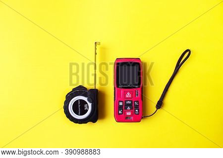 Laser Rangefinder And Measuring Tape On Yellow Background. The Measuring Devices Concept