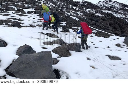 Several Climbers With Large Backpacks And Trekking Poles Go To The Top Of The Volcano. Mountain Clim