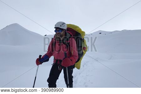 Smiling Climber In A Helmet, A Backpack And Trekking Poles Walks Along A Snow-covered Trail. Mountai
