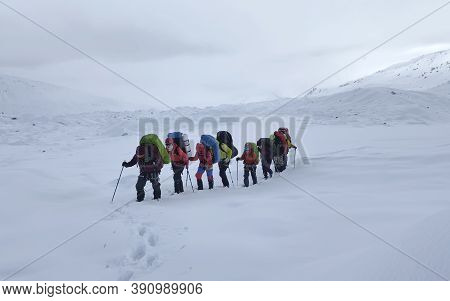 A Group Of Climbers With Backpacks And Trekking Poles Are Walking Along A Snow-covered Trail. Mounta