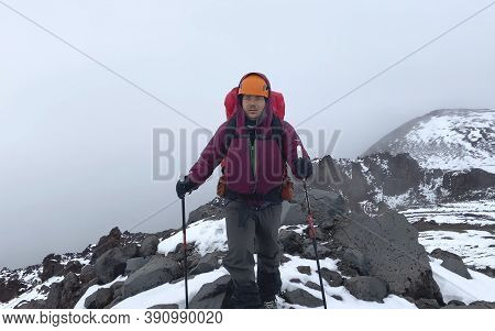 Tired Tourist With A Backpack And Trekking Poles Walks Along A Mountain Trail. Mountain Climbing. Tr