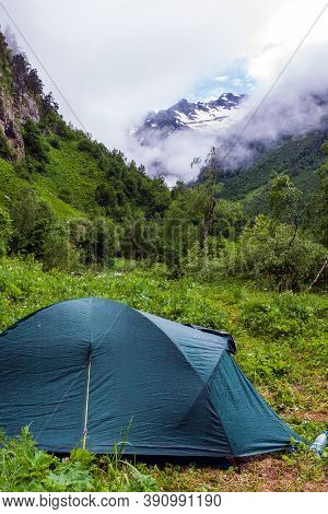 Caucasus Mountains, Russia. Tourist Tent On Glade In Imeretinka River Valley With Snowy Mountain Pea
