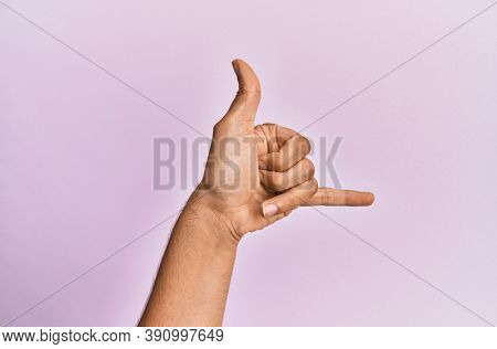 Arm and hand of caucasian young man over pink isolated background gesturing hawaiian shaka greeting gesture, telephone and communication symbol