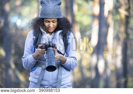 African American Woman In The Forest With A Camera. Shee Looks At Cameras Monitor. Close Up Photo.
